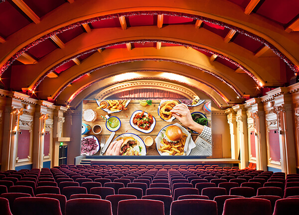 Inside of a cinema with Honest Burgers food on screen