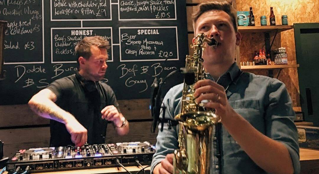 DJ and saxophonist inside an Honest Burger private event