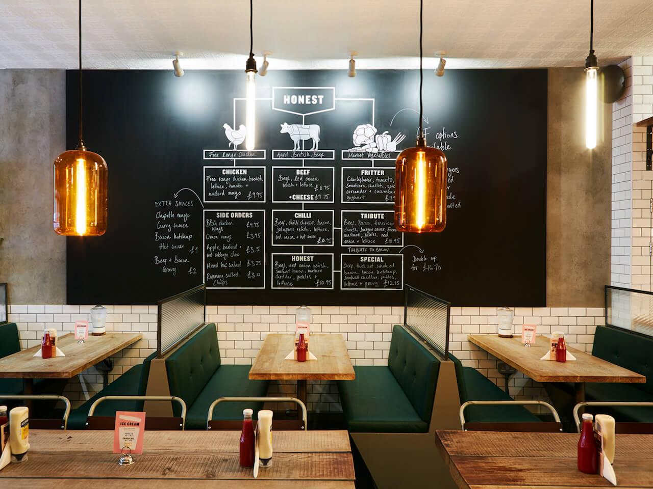 Booth seating and large blackboard menu inside Honest Burgers Ealing