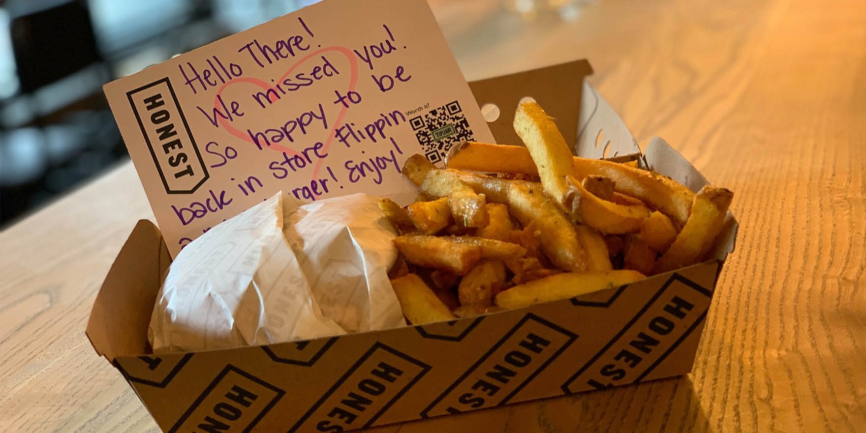 Honest Burgers takeout box, with burger, chips and a thankyou note