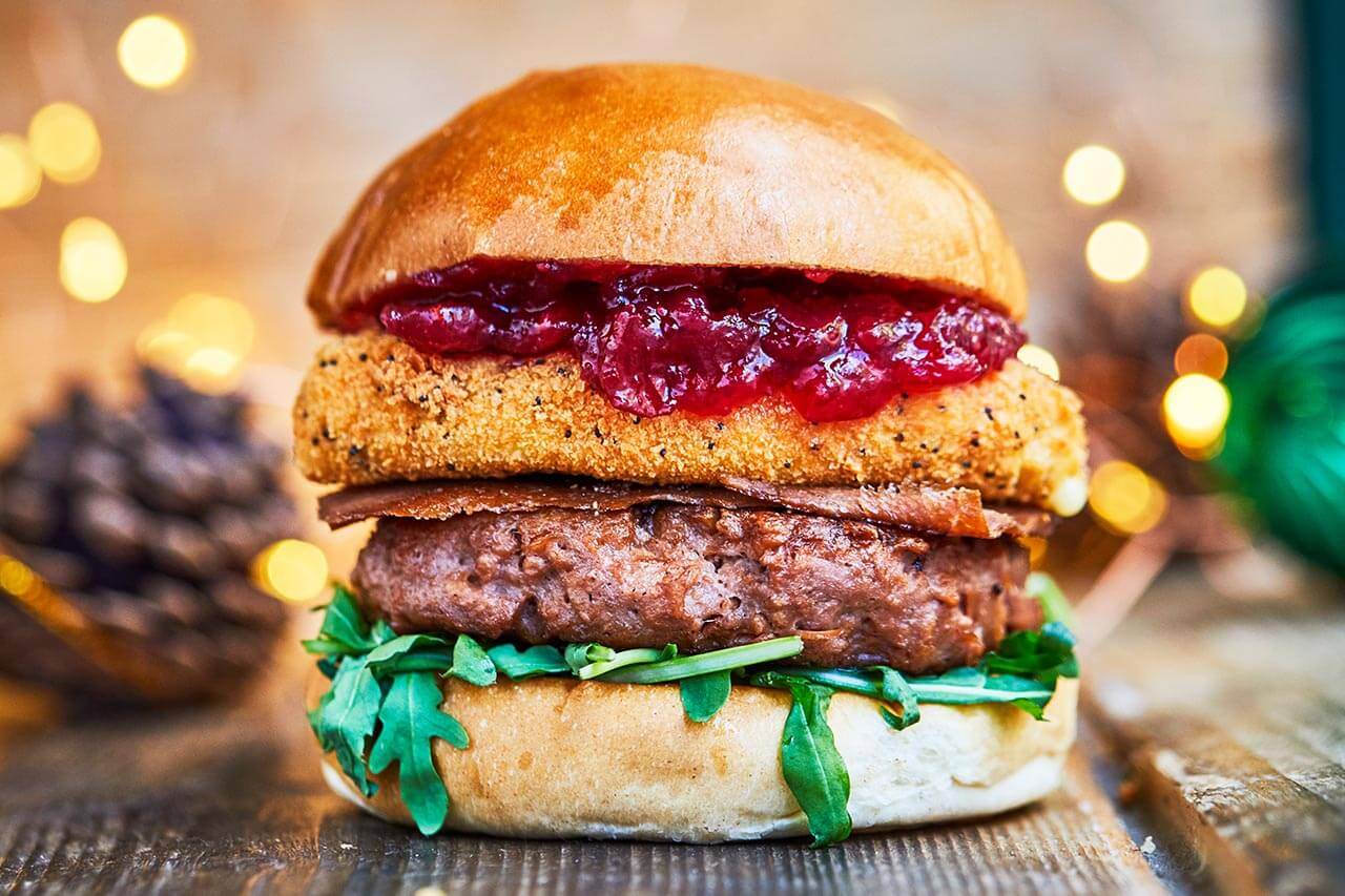 Christmas veggie beyond meat burger with deep fried camembert cheese and bacon