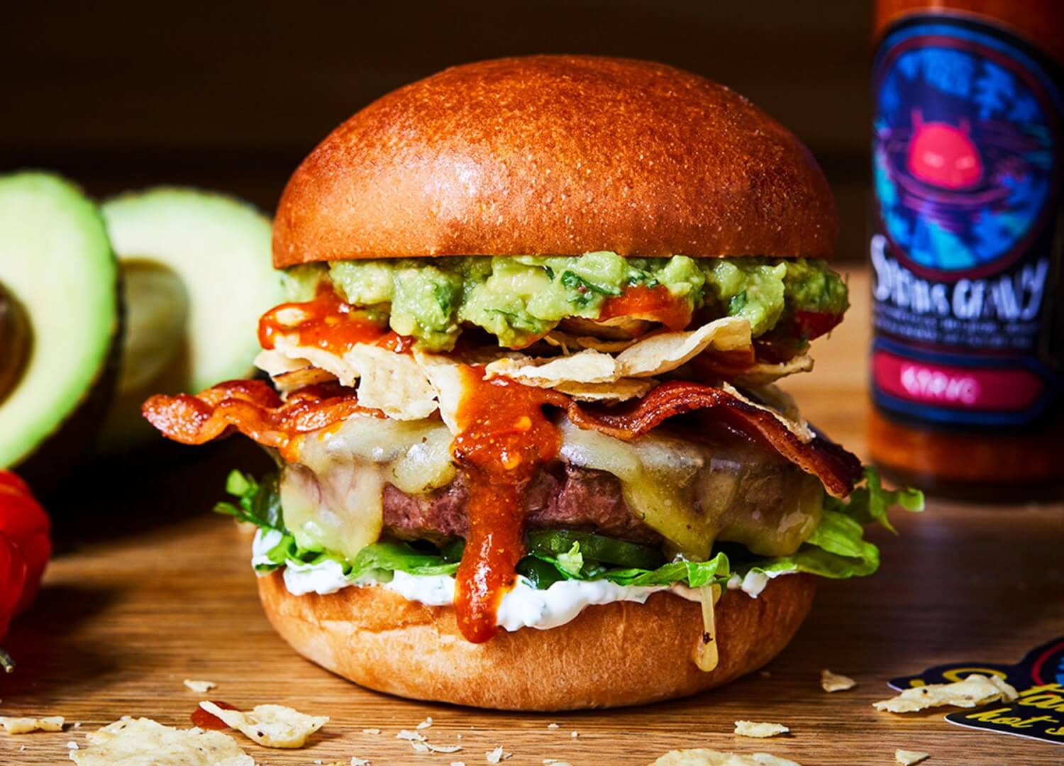 Honest beef burger with hot sauce, bacon, cheese, avocado and nachos